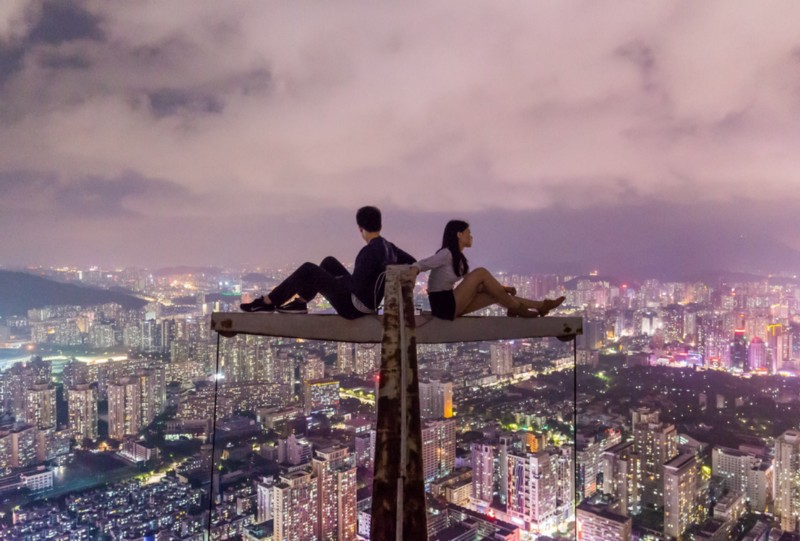 A male and a female sitting on a metal structure high above the night city