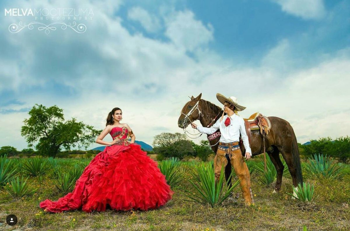 A woman standing in a red dress out in a field next to a man and a horse